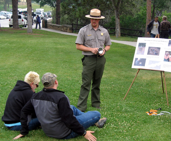 Ranger Charilie Baker giving a talk on the lawn of the visitor center to two park visitors.