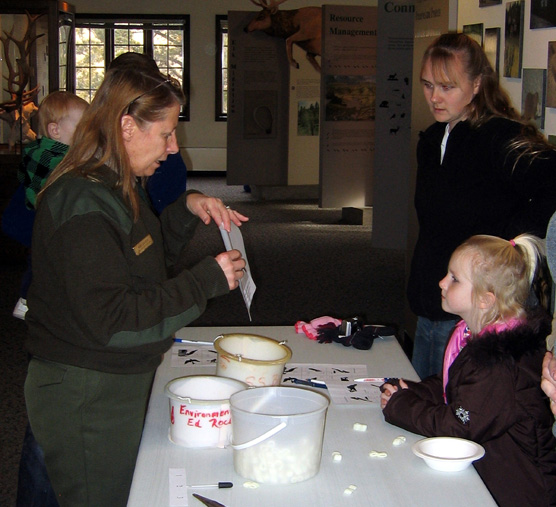 Ranger Mary Laycock stands by a table explaining different ways birds feed to Kaiya Schlecht and her mother Laurie.