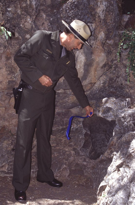 Surveying tape held by Ranger Mike Laycock blows in the wind at the natural entrance to Wind Cave.