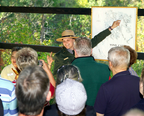 Ranger Tammy Wright points to a map of Wind Cave while standing in front of a tour.