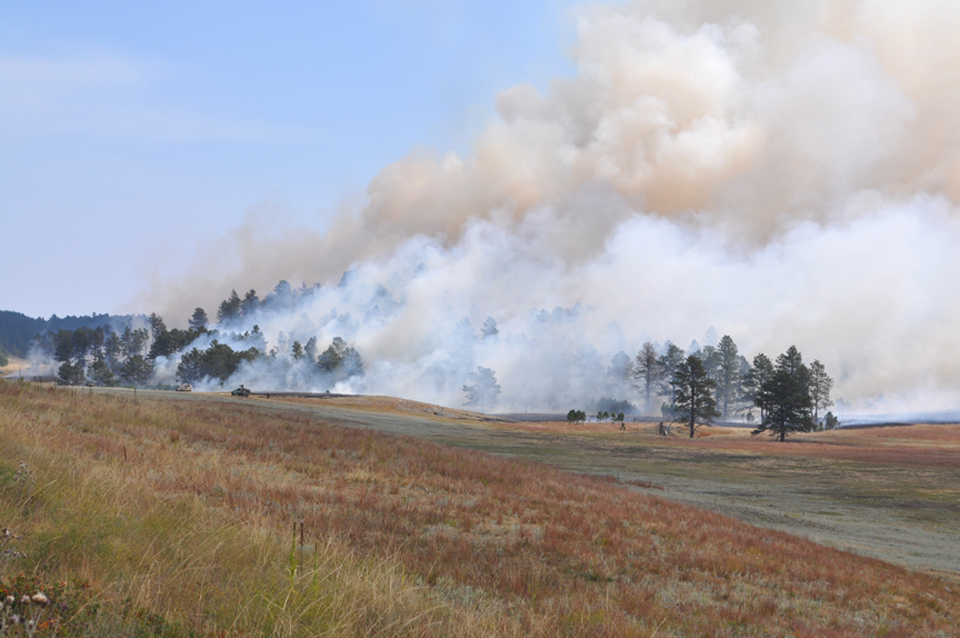 Smoke rising from a fire burning in grass and timber.
