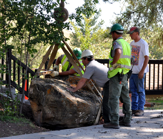 Wind Cave maintenance employees (from left) Jeff Simmons, Steve Schrempp, Mike Carder, and the JK Crane Service operator position the boulder to be used to hold the plaque.