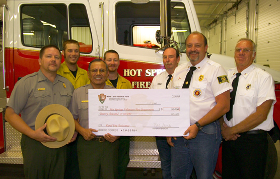 Employees from Wind Cave National Park present a symbolic check to Hot Springs Fire Department representatives.