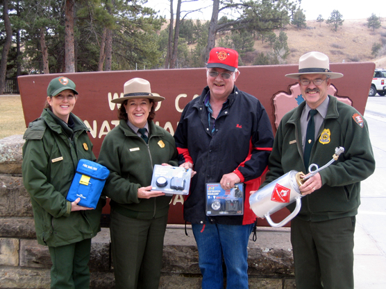 Displaying examples of equipment bought with grant money are, left to right, Supervisory Forestry Technician Sabrina Henry, Park Superintendent Linda L. Stoll, Pringle Fire Chief Bob Whitney, and Chief Ranger Rick Mossman.