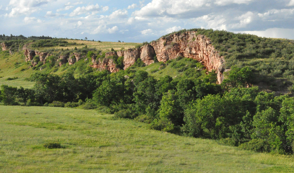 Sanson Buffalo Jump seen from a distance. Rock cliff towering over a green valley.