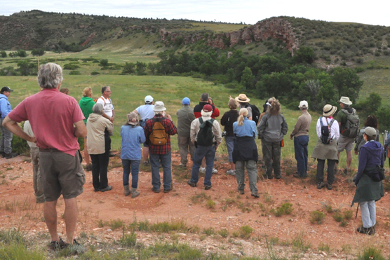 People standing listening to a park ranger with the buffalo jump in the distance.