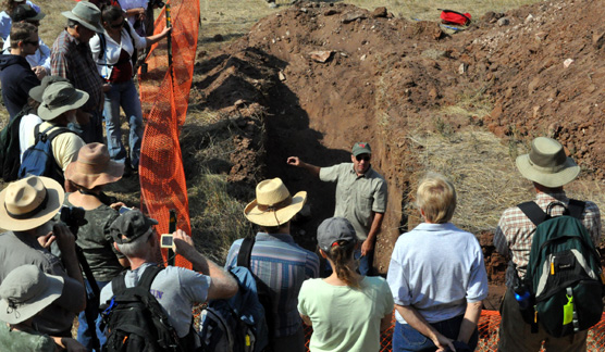 Archeologist Timothy Schilling stands in a trench surrounded by visitors as he describes the bones found in a trench at the Sanson Buffalo Jump.