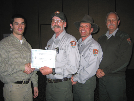 Photo showing Bret Graves, Environmental Project Scientist, DENR, presenting the award and receiving it are (left to right) Steve White, Maintenance Mechanic, Mike Carder, Maintenance Worker, and Jeff Simmons, Mason.
