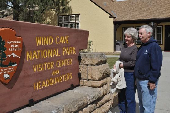 Mary and John Bertucci standing in front of the visitor entrance sign at Wind Cave National Park.
