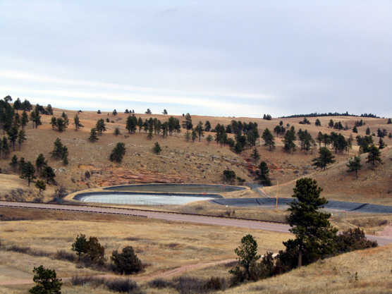 Photograph of existing wastewater treatment lagoons. Three new lagoons will be constructed on the ridge in the background.