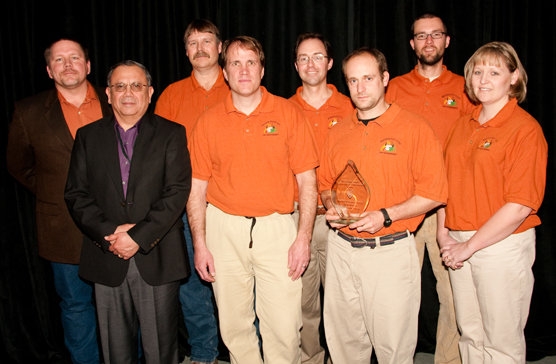A photo showing a group of people standing in front of the camera. Accepting the award, from left to right, are: Jim McMahill, park superintendent Vidal Davila, Al Stover, Eric Allen, Dan Swanson, Kenn Perreault, Jon Freeman, and Angie Nellen.