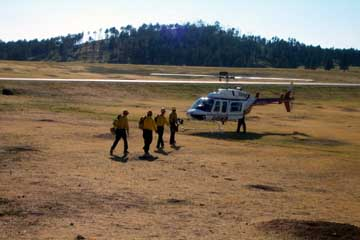 Fire crew members loading onto a helicopter preparing to be delivered to the Curley Canyon Fire.