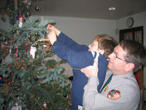 Park Employee Steve Schrempp helps his son Timothy decorate the park's Christmas tree at last year's open house.