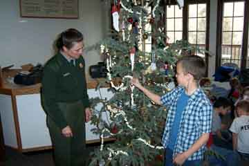 Park ranger and child decorate the tree.