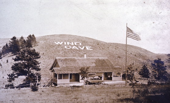 Photograph of the first Wind Cave visitor center and sign on hillside.