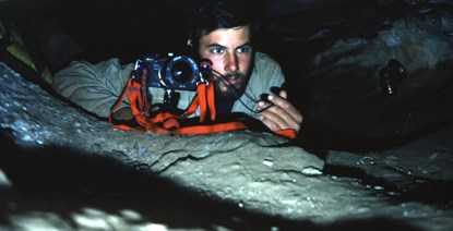 Park employee taking a photograph inside Wind Cave