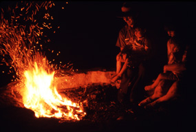 Visitors sit by an evening campfire.
