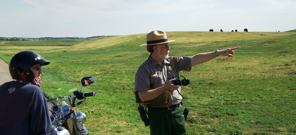 A visitor on a motorcycle looks at a ranger who is pointing across the prairie