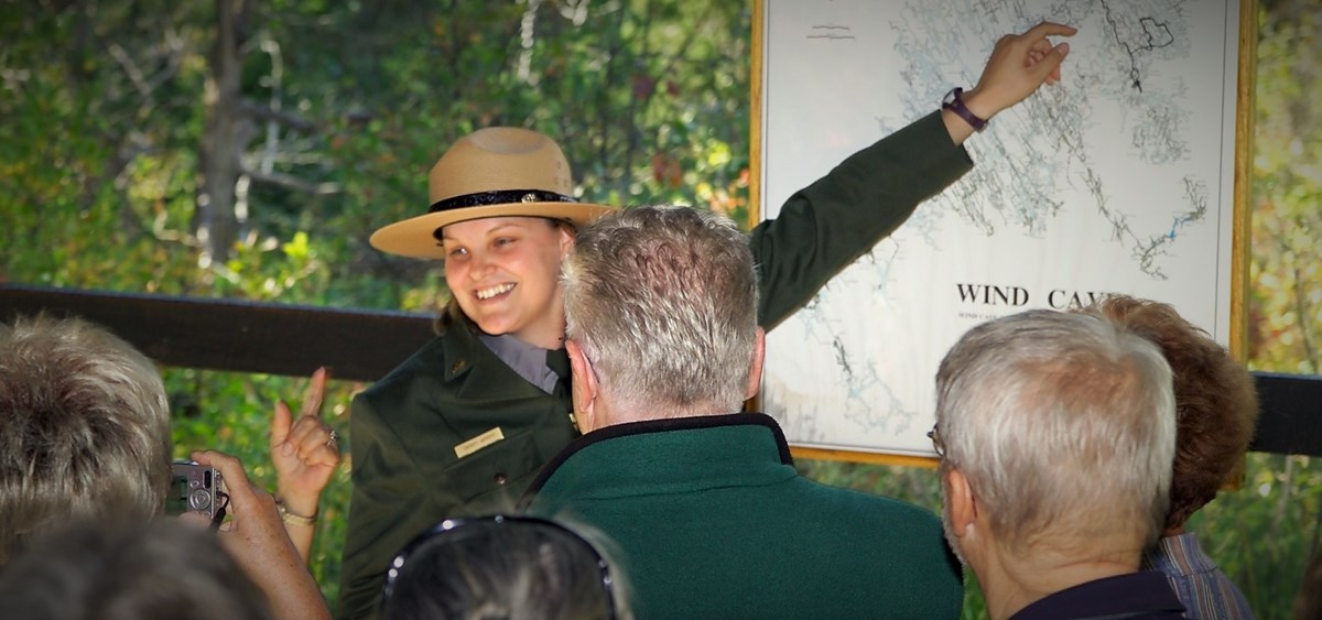 A ranger points to the Wind Cave map during a cave tour
