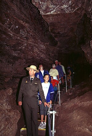 Ranger leading visitors down a stairway into the Model Room