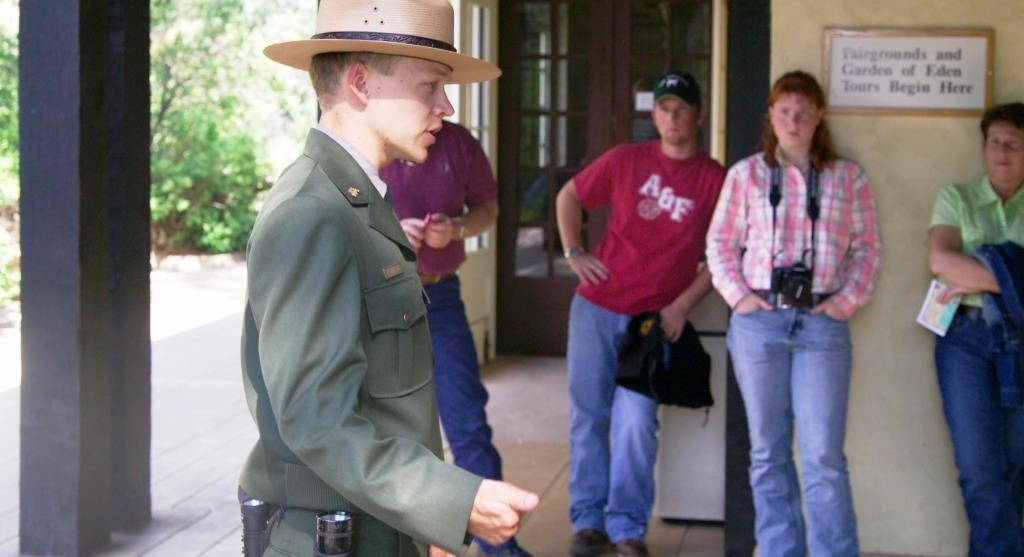 A uniformed park ranger is orienting visitors about proper cave safety.  There are four visitors around the ranger in a half circle.