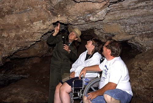 A ranger highlighting cave features to two visitors, one of whom is in a wheelchair.