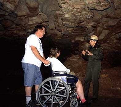 A ranger presenting an interpretive program to two visitors, one of whom is in a wheelchair.