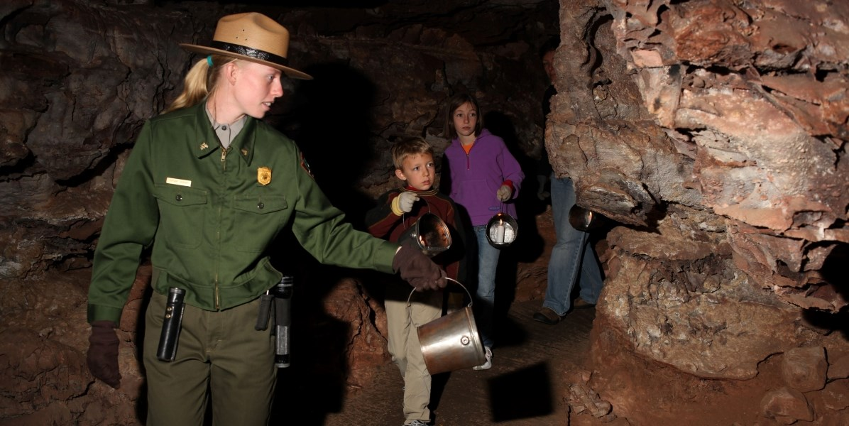 a ranger holding a bucket with a candle in it shining light on the cave with visitors