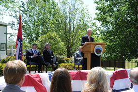Former President Clinton speaks at the dedication ceremony for the Clinton Birthplace Home. The two-story, white frame house is in the background.