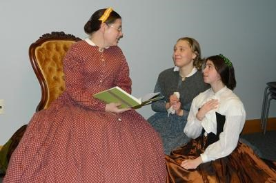 Three ladies dressed in Victorian period clothing, two are on the floor looking up at a woman sitting in a chair reading a book.