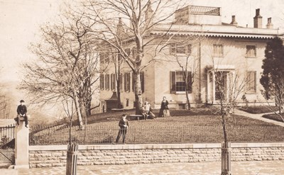 A large house with a wrought iron fence and children posing in the yard