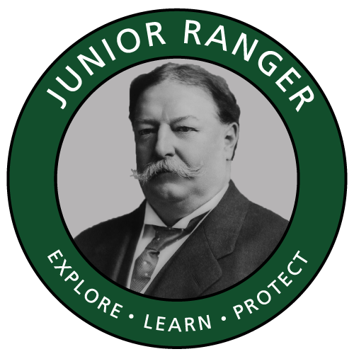 Green circle logo with picture of Taft in middle