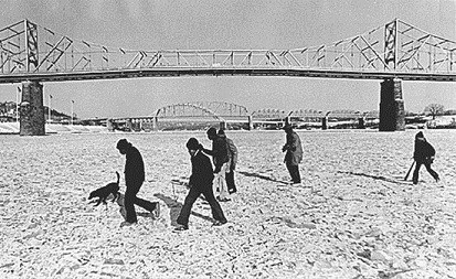 Several people walking across an icy surface with a suspension bridge in the background.
