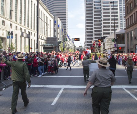 Several rangers in green pants, grey shirts and flat hats walk between crowds of people on sidewalks