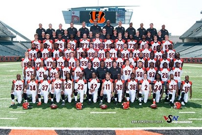 Several athletes in white and orange uniforms and coaches in black shirts pose for a team photo