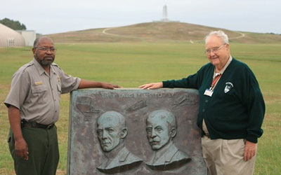 Park ranger and volunteer standing with a monument to the Wright Brothers near Kitty Hawk, North Carolina.