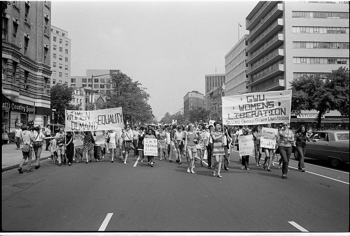 A historical photograph of the women's liberation movement with women with signs marching up a street.