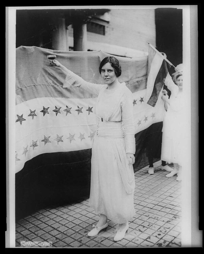 Alice Paul standing next to the Suffrage Flag holding a glass in a toast salute.