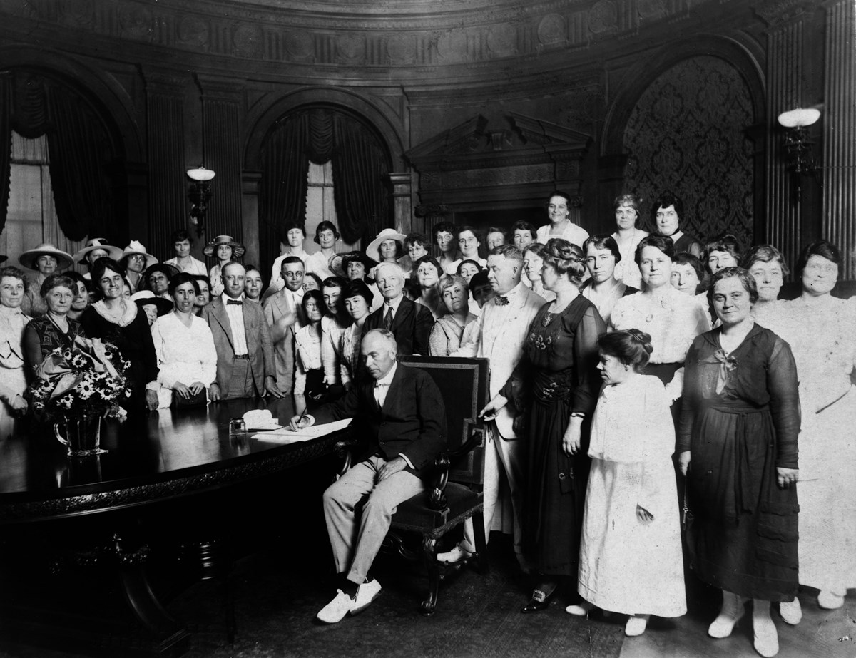 A historical photograph of a man in a crowded room surrounded by people signing a document.