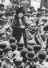 Harriot Stanton Blatch giving a speech in a crowd of men wearing hats.