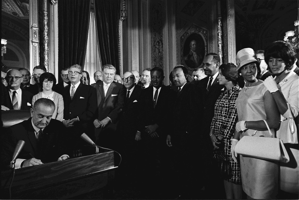 Historical photograph of Lyndon Johnson signing Voting Rights Act.
