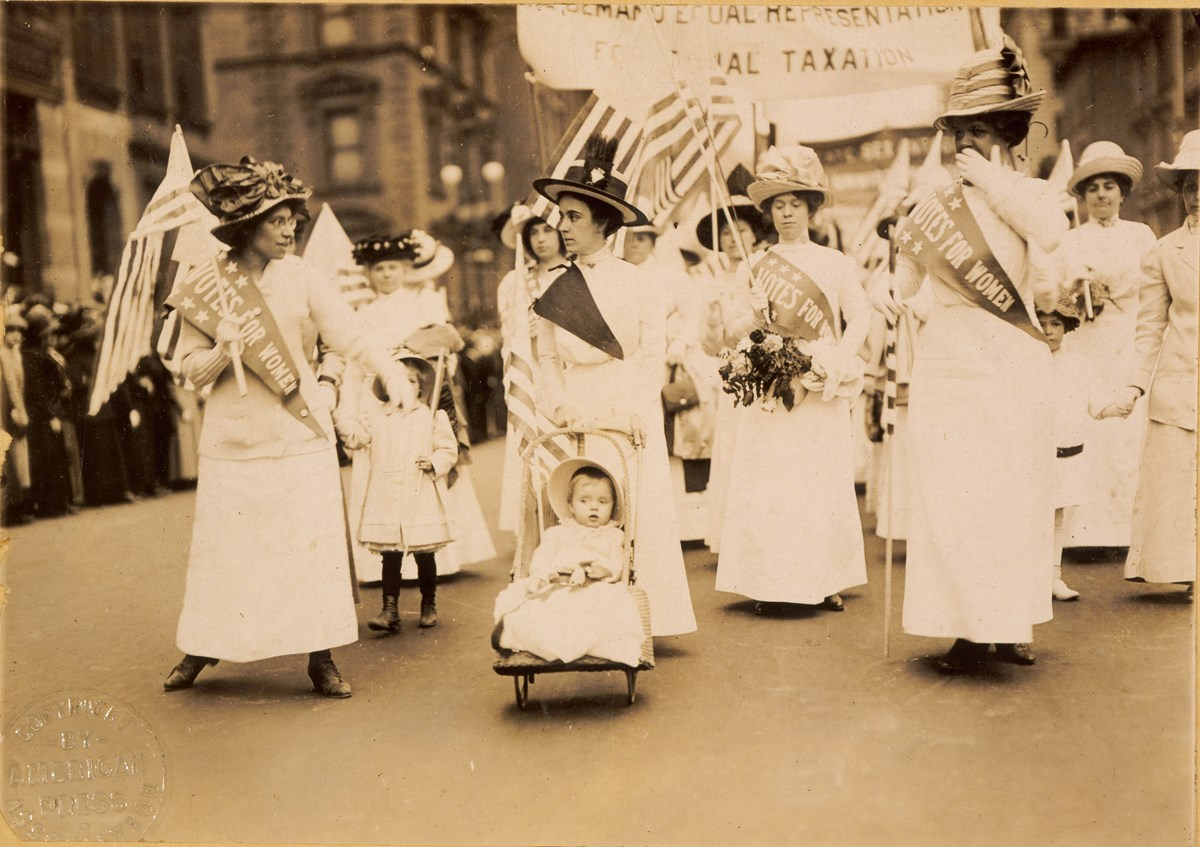 Historical photograph of women marching down a busy street in support of suffrage.