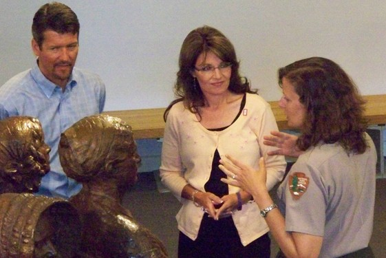Governor Palin listens to park superintendent Orcutt explain who organized the First Woman's Rights Convention. They are standing next to life-size statues.