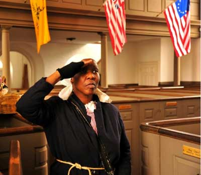 Carolyn Evans as Harriet Tubman saluting in a church