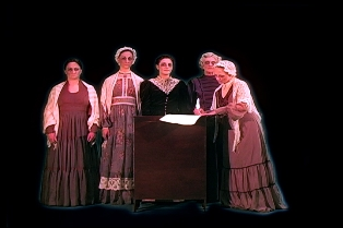 Five women, dressed in 1800's clothing, are gathered around a central figure reading.
