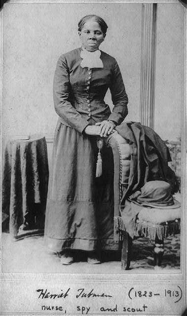 Harriet Tubman standing next to a chair