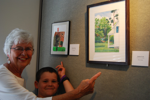 Abby Gazley, Seneca Falls, and her grandson, Eli Kupiec, Amsterdam, the Netherlands, point to their paintings of the Stanton House