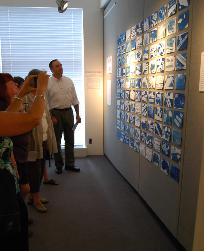 several participants viewing wall of art at opening