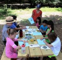 A ranger leads an activity for Junior Ranger Day at a picnic table