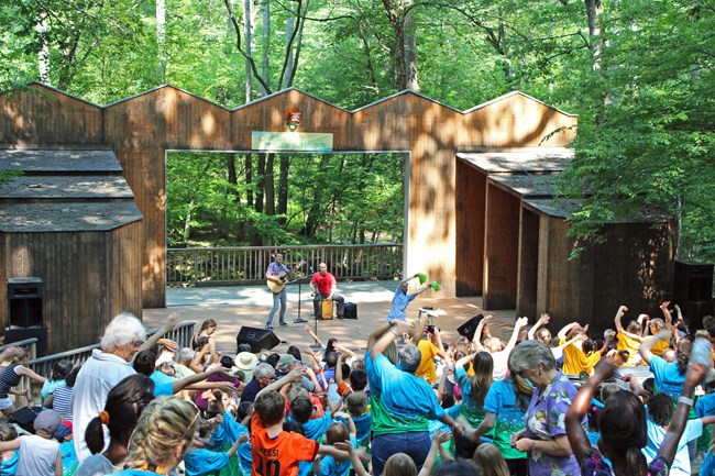 A Theatre-in-the-Woods performance with artist on stage and a full audience